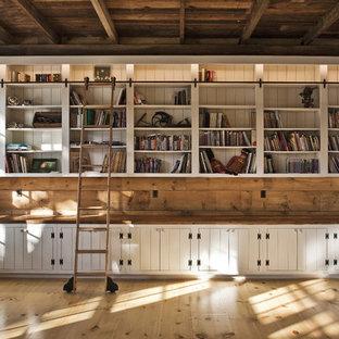 Diseño de sala de estar con biblioteca de estilo de casa de campo con suelo de madera en tonos medios