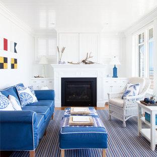 Réalisation d'une salle de séjour marine avec un mur blanc, un sol en bois brun, une cheminée standard, un sol marron et un téléviseur dissimulé.