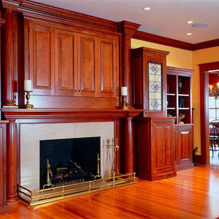 Family room - huge traditional medium tone wood floor family room idea in Boston with yellow walls, a standard fireplace, a stone fireplace and a concealed tv
