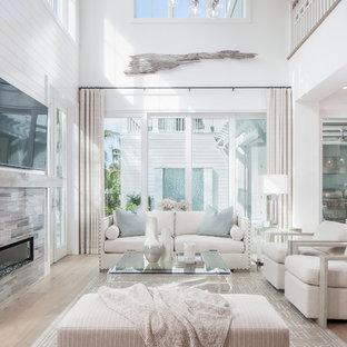 Diseño de sala de estar abierta, marinera, con paredes blancas, suelo de madera clara, chimenea lineal, marco de chimenea de baldosas y/o azulejos y televisor colgado en la pared