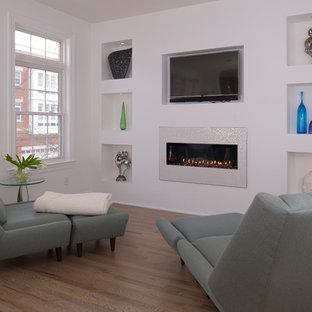 ワシントンD.C.のコンテンポラリースタイルのおしゃれなオープンリビング (白い壁、淡色無垢フローリング、標準型暖炉、漆喰の暖炉まわり、埋込式メディアウォール) の写真