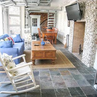 チャールストンの大きいビーチスタイルのおしゃれなファミリールーム (白い壁、スレートの床、標準型暖炉、壁掛け型テレビ、マルチカラーの床) の写真