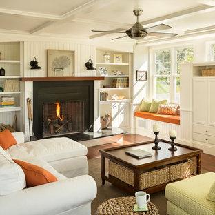 Ejemplo de sala de estar costera, de tamaño medio, con paredes blancas, suelo de madera en tonos medios, chimenea tradicional y televisor retractable