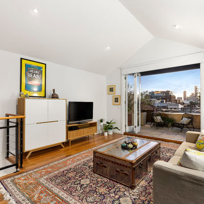 Example of a mid-sized trendy loft-style medium tone wood floor family room design in Melbourne with white walls, no fireplace and a tv stand