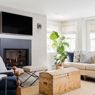 Modelo de sala de estar costera con paredes beige, suelo de cemento y televisor colgado en la pared
