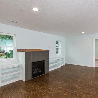 ポートランドの中サイズのコンテンポラリースタイルのおしゃれなファミリールーム (茶色い壁、コルクフローリング、標準型暖炉、タイルの暖炉まわり、壁掛け型テレビ) の写真