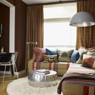Family room - eclectic family room idea in New York with brown walls and no fireplace
