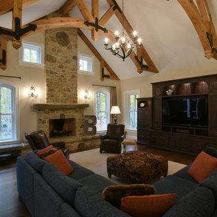 Esempio di un grande soggiorno tradizionale aperto con pareti gialle, pavimento in legno massello medio, camino classico, cornice del camino in pietra e parete attrezzata