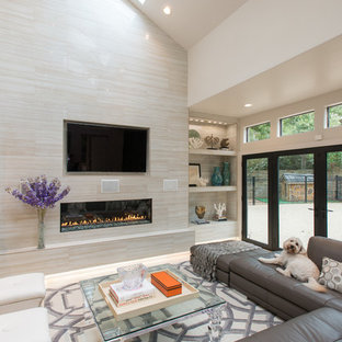 Example of a large minimalist travertine floor family room design in Houston with beige walls, a standard fireplace, a tile fireplace and a wall-mounted tv