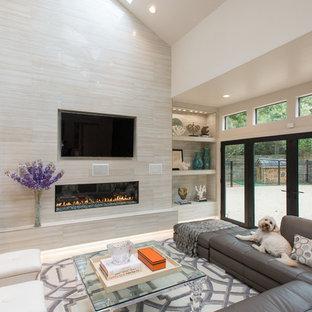 Inspiration pour une grande salle de séjour minimaliste avec un mur beige, un sol en travertin, une cheminée standard, un manteau de cheminée en carrelage et un téléviseur fixé au mur.