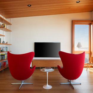 Imagen de sala de estar con biblioteca actual, de tamaño medio, con paredes blancas, televisor colgado en la pared, suelo de madera en tonos medios y chimenea lineal