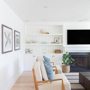 オレンジカウンティのビーチスタイルのおしゃれな独立型ファミリールーム (白い壁、淡色無垢フローリング、標準型暖炉、石材の暖炉まわり、埋込式メディアウォール、白い床) の写真