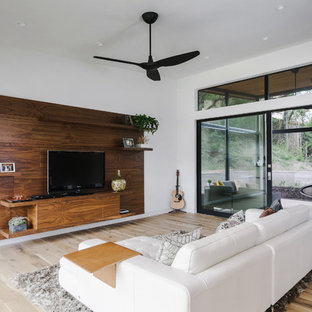 Large minimalist open concept light wood floor and brown floor family room photo in Austin with white walls, no fireplace and a tv stand