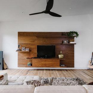 Diseño de sala de estar abierta, minimalista, grande, sin chimenea, con paredes blancas, suelo de madera clara, televisor independiente y suelo marrón