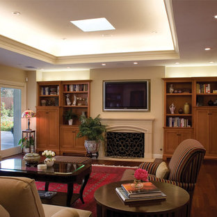 Example of a classic open concept dark wood floor family room design in Los Angeles with beige walls, a standard fireplace and a wall-mounted tv