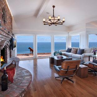 Cette photo montre une grand salle de séjour craftsman fermée avec un mur blanc, un sol en bois clair, une cheminée standard, un manteau de cheminée en brique, un téléviseur fixé au mur et un sol beige.