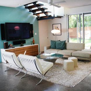 オースティンのコンテンポラリースタイルのおしゃれなファミリールーム (コンクリートの床、暖炉なし、壁掛け型テレビ、マルチカラーの壁) の写真