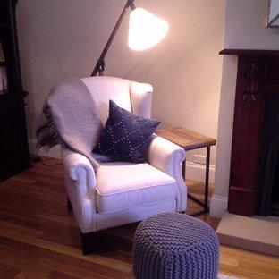 Idee per un piccolo soggiorno classico aperto con libreria, pareti beige, parquet chiaro, camino classico, cornice del camino in legno e nessuna TV