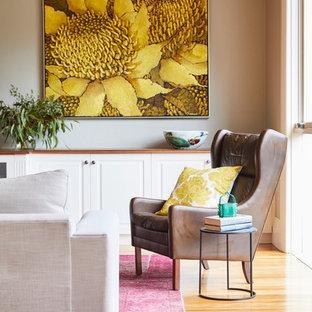Esempio di un grande soggiorno boho chic aperto con libreria, pareti beige, pavimento in legno massello medio, nessun camino, TV a parete e pavimento marrone