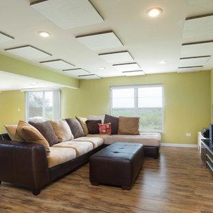Cette image montre une grand salle de séjour design ouverte avec un mur vert, un sol en bois brun, aucune cheminée et un téléviseur indépendant.