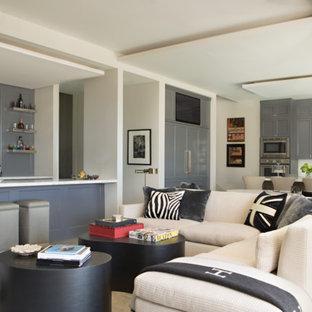 Esempio di un soggiorno classico di medie dimensioni e aperto con angolo bar, pareti bianche, pavimento in cemento, parete attrezzata, nessun camino e pavimento beige