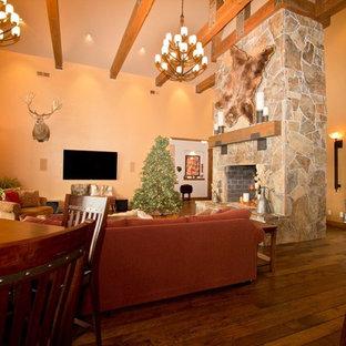 Imagen de sala de estar rural con paredes beige, suelo de travertino, chimenea de doble cara, marco de chimenea de piedra y televisor colgado en la pared