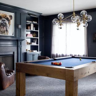 Immagine di un ampio soggiorno tradizionale aperto con sala giochi, pareti blu, parquet scuro, camino classico, cornice del camino in pietra, TV a parete e pavimento marrone