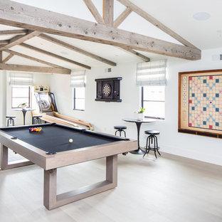 Aménagement d'une grand salle de séjour méditerranéenne ouverte avec salle de jeu, un mur blanc, un sol en bois clair et un téléviseur fixé au mur.