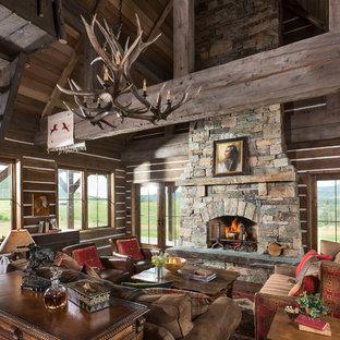 Imagen de sala de estar abierta, rural, grande, sin televisor, con chimenea tradicional, marco de chimenea de piedra y paredes marrones