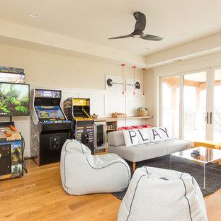 Immagine di un grande soggiorno minimal con sala giochi, pareti bianche, parquet chiaro e parete attrezzata