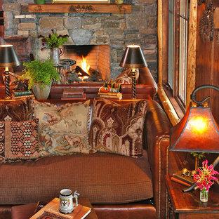 シャーロットの大きいラスティックスタイルのおしゃれなファミリールーム (ライブラリー、茶色い壁、無垢フローリング、標準型暖炉、石材の暖炉まわり、テレビなし) の写真