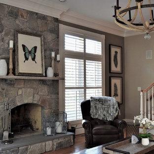 ワシントンD.C.の広いラスティックスタイルのおしゃれなオープンリビング (グレーの壁、無垢フローリング、標準型暖炉、石材の暖炉まわり、コーナー型テレビ) の写真