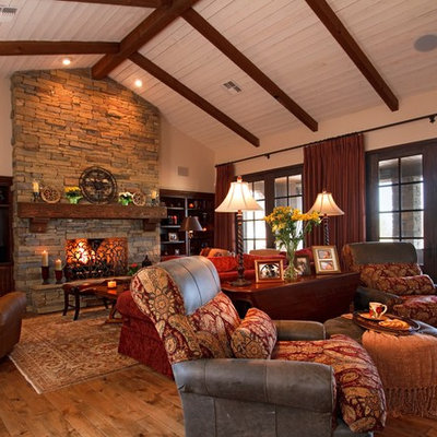 Family room - rustic open concept medium tone wood floor family room idea in Phoenix with beige walls, a standard fireplace, a stone fireplace and a media wall
