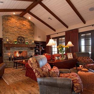 Modelo de sala de estar abierta, rústica, con paredes beige, suelo de madera en tonos medios, chimenea tradicional, marco de chimenea de piedra y pared multimedia