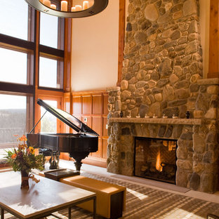 Example of a mountain style family room design in Santa Barbara with a music area, beige walls, a standard fireplace, a stone fireplace and no tv