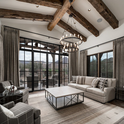 Family room - huge rustic open concept medium tone wood floor and brown floor family room idea in Phoenix with white walls, a standard fireplace, a stone fireplace and a media wall