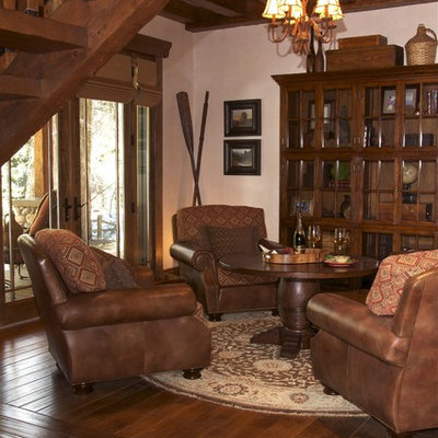 Example of a mountain style dark wood floor family room design in San Diego with beige walls