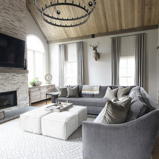 ナッシュビルの大きいトランジショナルスタイルのおしゃれなファミリールーム (ベージュの壁、無垢フローリング、標準型暖炉、石材の暖炉まわり、壁掛け型テレビ) の写真