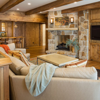 Mountain style open concept medium tone wood floor and brown floor family room photo in Minneapolis with a bar, brown walls, a corner fireplace, a stone fireplace and a media wall