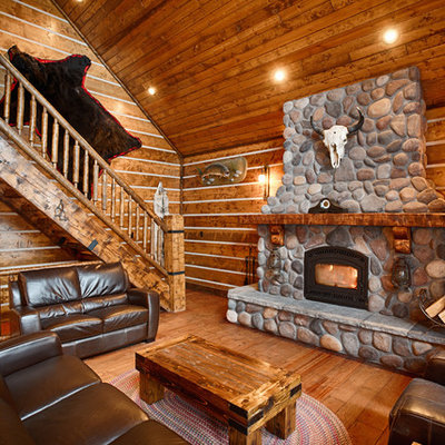 Inspiration for a large rustic enclosed dark wood floor and brown floor family room remodel in Other with brown walls, a wood stove, a stone fireplace and a wall-mounted tv
