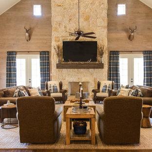 Idées déco pour une grande salle de séjour montagne ouverte avec un sol en bois brun, une cheminée standard, un manteau de cheminée en pierre, un téléviseur fixé au mur, un mur beige et un sol marron.