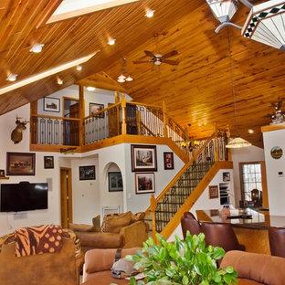 他の地域の中くらいのラスティックスタイルのおしゃれなオープンリビング (白い壁、セラミックタイルの床、薪ストーブ、石材の暖炉まわり、壁掛け型テレビ、ベージュの床) の写真