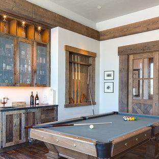 Diseño de sala de juegos en casa rústica con paredes blancas y suelo de madera oscura