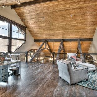 Modelo de sala de estar con barra de bar tipo loft, rural, extra grande, sin televisor, con paredes beige y suelo de madera en tonos medios