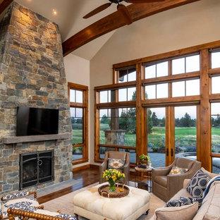 Inspiration pour une grande salle de séjour chalet ouverte avec un mur beige, une cheminée standard, un manteau de cheminée en pierre, un téléviseur fixé au mur, un sol en bois foncé et un sol marron.