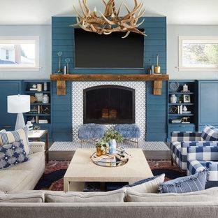 シカゴのトランジショナルスタイルのおしゃれなファミリールーム (青い壁、濃色無垢フローリング、標準型暖炉、タイルの暖炉まわり、壁掛け型テレビ) の写真