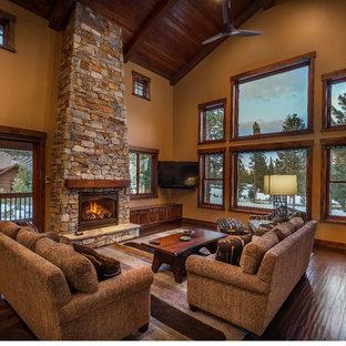 サクラメントの巨大なラスティックスタイルのおしゃれなオープンリビング (茶色い壁、濃色無垢フローリング、標準型暖炉、石材の暖炉まわり、コーナー型テレビ) の写真