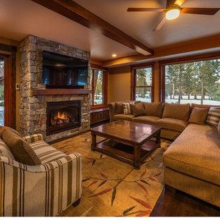 サクラメントの広いラスティックスタイルのおしゃれなオープンリビング (茶色い壁、濃色無垢フローリング、標準型暖炉、石材の暖炉まわり、壁掛け型テレビ) の写真