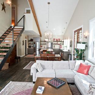 Inspiration pour une grand salle de séjour rustique ouverte avec un téléviseur fixé au mur, un mur beige, un sol en bois foncé, un poêle à bois et un manteau de cheminée en métal.