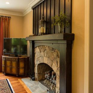 Inspiration pour une salle de séjour chalet ouverte avec un mur jaune, un sol en bois brun, une cheminée standard, un manteau de cheminée en pierre et un téléviseur indépendant.